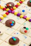 Still life of white chocolate with smarties. Inside, indoors, interiors, food, nutrition, nourishment, milk, bar, candy, confections, confectionery, sweet stock images