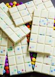 Still life of white chocolate with smarties. Inside, indoor, indoors, interior, interiors, food, nutritive, nutrition, nourishment, chocolates, bar, bars stock photography