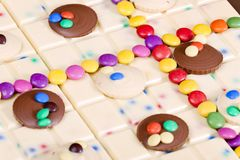 Still life of white chocolate with smarties. Inside, indoors, interiors, food, nutrition, nourishment, milk, bar, candy, confections, confectionery, sweet royalty free stock image