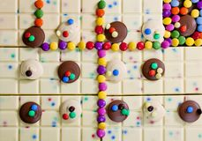 Still life of white chocolate with smarties. Inside, indoors, interiors, food, nutrition, nourishment, milk, bar, candy, confections, confectionery, sweet stock photo