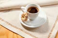 Still life with a white cup of coffee with foam at the background of the vintage homemade napkin Stock Image