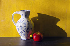 Still-life with white jug and red apple Stock Images