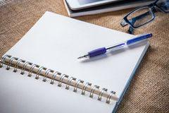 Still life of white paper note book page with writing pen lying. On table top and eye glasses beside use for education and studying theme Royalty Free Stock Photography