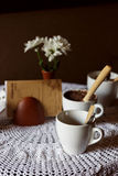 Still life. White porcelain cups and a vase of flowers stand on a table with a white tablecloth in a brown cafe hall Royalty Free Stock Photography