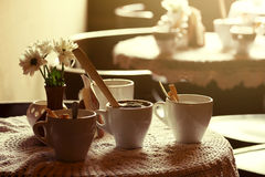 Still life. White porcelain cups and a vase of flowers stand on a table with a white tablecloth in a brown cafe hall Stock Images