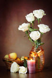 Still life with white roses in the vase and a burning candle Royalty Free Stock Photos
