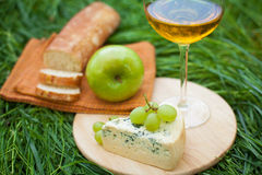 Still life with white wine, baguette, cheese, grape and apple. On the grass Stock Photo