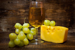 Still life with white wine , cheese and grapes. On a wooden background royalty free stock images