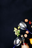 The still life with white wine in glass bottle on black background. Glasses of wine with fresh grapes. Bottle and footed glass. Fr Stock Photos