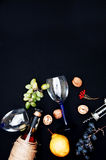 The still life with white wine in glass bottle on black background. Glasses of wine with fresh grapes. Bottle and footed glass. Fr Stock Photo