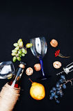The still life with white wine in glass bottle on black background. Glasses of wine with fresh grapes. Bottle and footed glass. Fr Stock Image