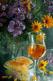 Still-life with white wine, honey and a bouquet. Still-life with white wine, honey in honeycombs and a magnificent bouquet royalty free stock photography