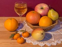 Still life with white wine and juicy ripe fruit in a wicker basket. Stock Image