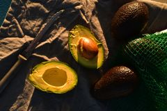 Ripe avocado cut into halves. Still life with whole avocados and one avocado cut into halves Stock Images