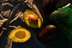 Ripe avocado cut into halves. Still life with whole avocados and one avocado cut into halves Stock Photos