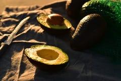Ripe avocado cut into halves. Still life with whole avocados and one avocado cut into halves Royalty Free Stock Image