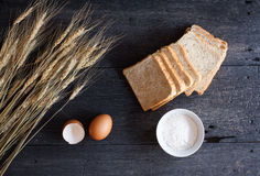 Still life with whole wheat bread, wheat ,egg,and flour on old w Stock Photos