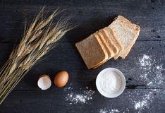 Still life with whole wheat bread, wheat ,egg,and flour on old w Stock Photo