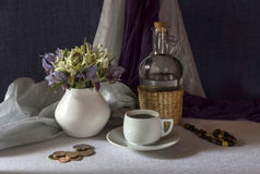 The still life with wild irises. Wild irises in a vase and a white cup of coffee on a table closeup Stock Photos