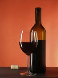 Still-life with wine bottle and glass. Over deep red background stock photos