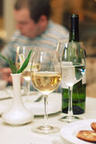 Still life wine bottle and glass. Green bottle of wine and two glasses with champagne and water on table in restaurant Royalty Free Stock Photography