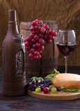 Still life with wine bottle, glass and grapes Royalty Free Stock Photography