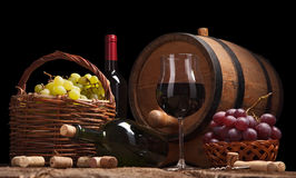 Still life with wine bottles, glasses and oak barrels Stock Images