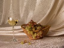 Still-life with a wine glass. Of white wine and a cluster of grapes on a light background Royalty Free Stock Images