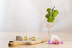 Still life with wine glass, cheese and blossom Stock Photo