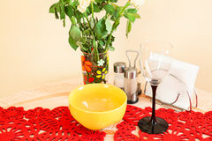Still life with wine glass, plate and flowers on kitchen table Royalty Free Stock Photos