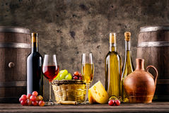Still life with wine, grapes, barrels and cheese Royalty Free Stock Photos