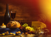 Still life with wine, grapes, bread and various sorts of cheese. Stock Photo