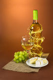 Still life with wine, grapes and cheese on the brown Royalty Free Stock Image