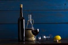 Still life with wine and lemon. Wine, lemon, wine glasses on a wooden background, studio lighting Stock Photography