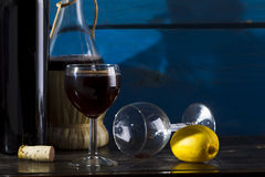 Still life with wine and lemon. Wine, lemon, wine glasses on a wooden background, studio lighting Royalty Free Stock Photography