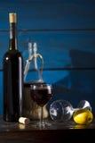 Still life with wine and lemon. Wine, lemon, wine glasses on a wooden background, studio lighting Stock Photo