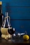 Still life with wine and lemon. Wine, lemon, wine glasses on a wooden background, studio lighting Royalty Free Stock Photo