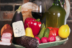 Still life with wine and some fruits,. Vegetables, cheese and ham. Against the backdrop of a brick wall Royalty Free Stock Photo