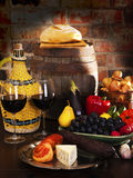 Still life with wine and some fruits,vegetables,. Cheese and ham. Against the backdrop of a brick wall Royalty Free Stock Photography