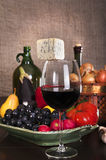Still life with wine and some fruits,vegetables,. Cheese and ham. Against the backdrop of a brick wall Stock Photos