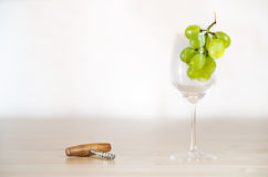 Still life with wineglass and a corkscrew. Bright still life photo of wineglass with grape and corkscrew on white background Stock Photos