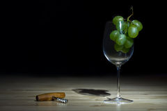 Still life with wineglass and a corkscrew. Dark still life photo of wineglass with grape and corkscrew on black background Royalty Free Stock Images