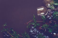 Still life with wineglasses, bottles, grapes and leaves Stock Photo