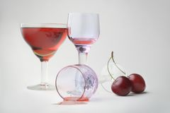 Still-life with wineglasses and cherries. Still-life with wineglasses of red beverage and cherries on the grey background Stock Image