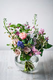 Still life. a wooden antique table, glass vase with Mixed bouquet. beautiful flowers Royalty Free Stock Images