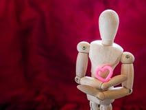 Still life wooden puppet and pink heart. Stock Photos