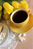 Still life. Yellow cup with tea in the background of a bouquet of yellow tulips and marshmallow on a white lace napkin Stock Photos