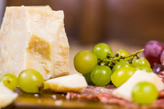 Still life - yellow and red muscat grape, cheese and salami Royalty Free Stock Image