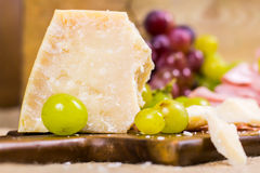 Still life - yellow and red muscat grape, cheese and salami on a wooden board Stock Photos