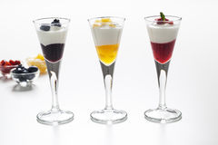 Still life of yogurt, berries, peach and jam. Still life of three cups with yogurt and three kinds of jam (blueberry, peach and strawberry) and decorative Royalty Free Stock Images